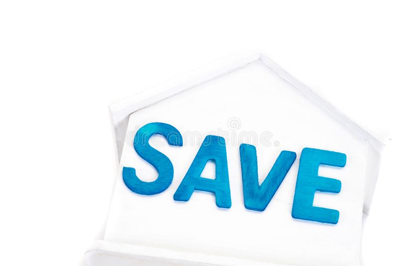 La palabra de ahorro en casa es hucha blanca en el fondo blanco Hora de invertir, propiedades inmobiliarias y concepto de la prop foto de archivo libre de regalías