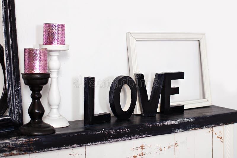 La palabra de madera es amor En la chimenea son dos palmatorias con las velas y el amor de madera de la palabra Inscripción del a foto de archivo