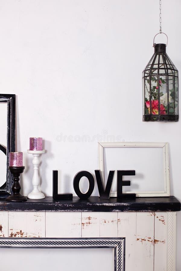 La palabra de madera es amor En la chimenea son dos palmatorias con las velas y el amor de madera de la palabra Inscripci?n del a imagen de archivo libre de regalías