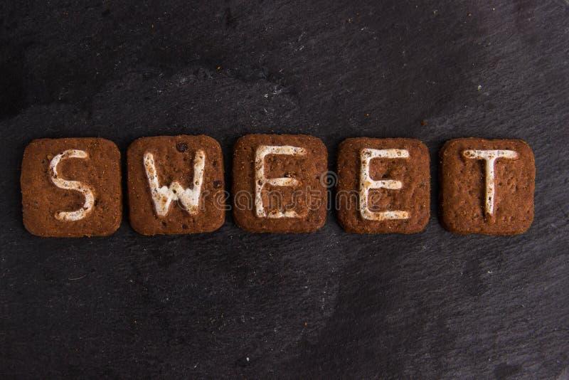 La palabra DULCE presentado con las letras de las galletas fotografía de archivo
