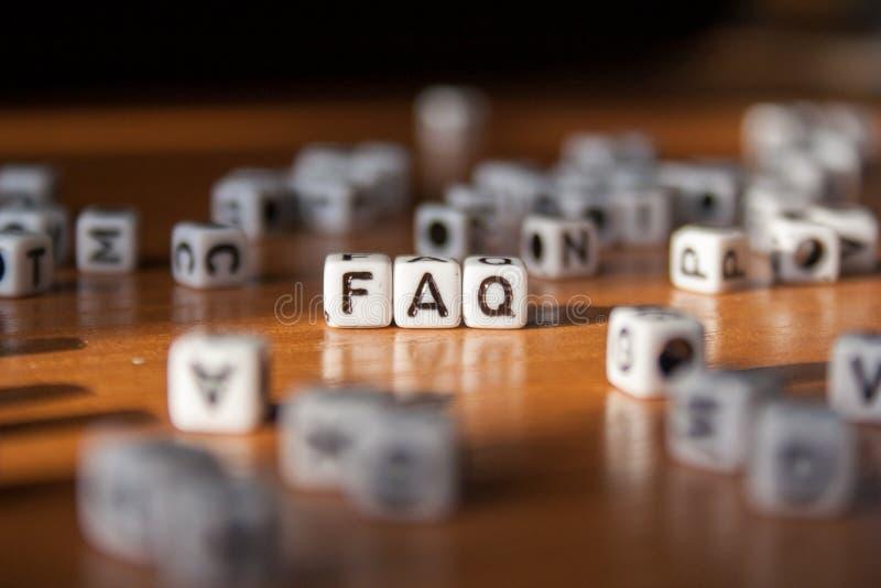 La palabra FAQ hecha de los bloques plásticos blancos en la tabla imagenes de archivo