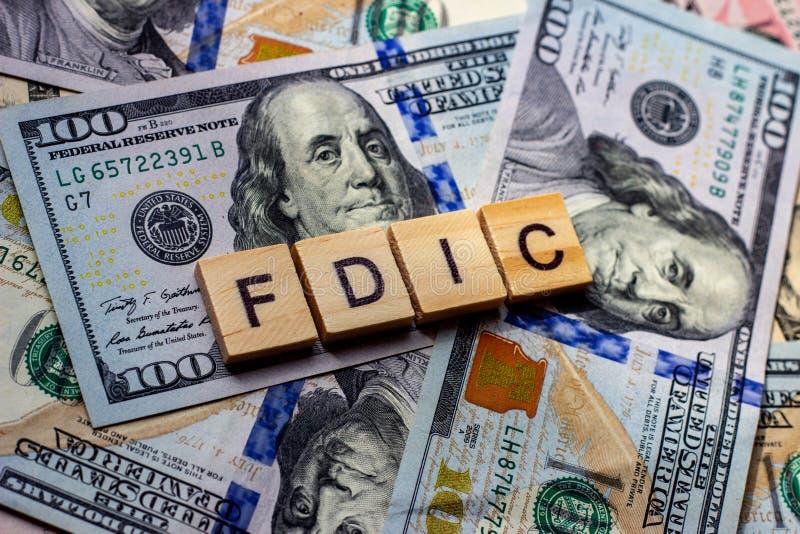 La palabra 'fdic' sobre los antecedentes de los dólares Concepto de la Corporación Federal de Seguros de Depósitos de Estados Uni imágenes de archivo libres de regalías