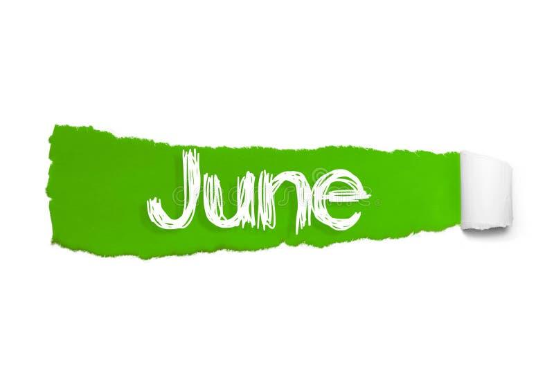 La palabra junio que aparece detrás del papel rasgado verde foto de archivo libre de regalías