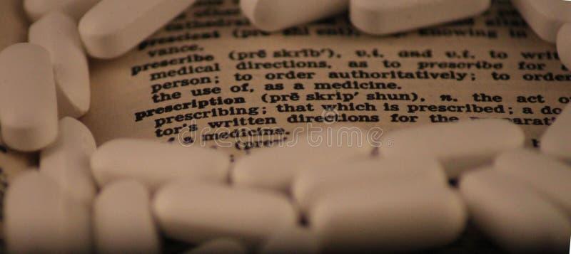La palabra para prescribe y prescripción rodeada por las píldoras blancas foto de archivo