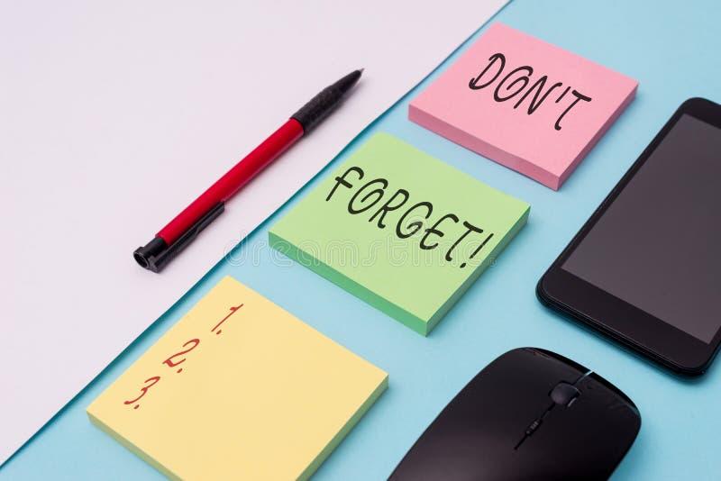 La palabra que escribe el texto Don T olvida Concepto del negocio para que utilizado recuerde alguien sobre los papeles de nota i fotografía de archivo