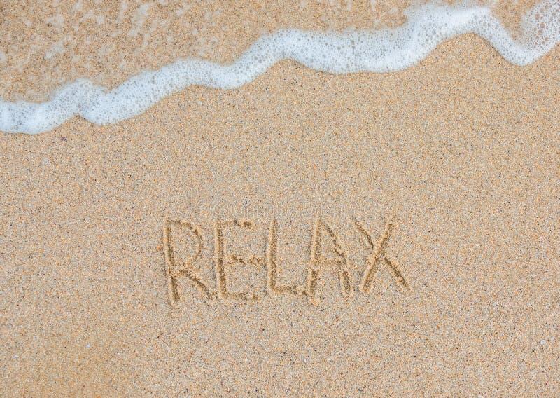 La palabra relaja manuscrito en la playa arenosa concepto del recorrido Vacaciones del tiempo de verano imágenes de archivo libres de regalías