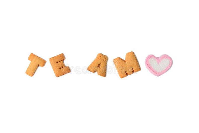 La palabra TE AMO Meaning TE AMO en español deletreada con alfabeto formó galletas y un caramelo en forma de corazón de la melcoc imágenes de archivo libres de regalías