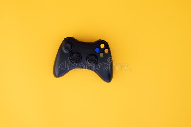La palanca de mando negra se aísla en un fondo amarillo Competencia del videojuego Concepto del juego fotos de archivo libres de regalías