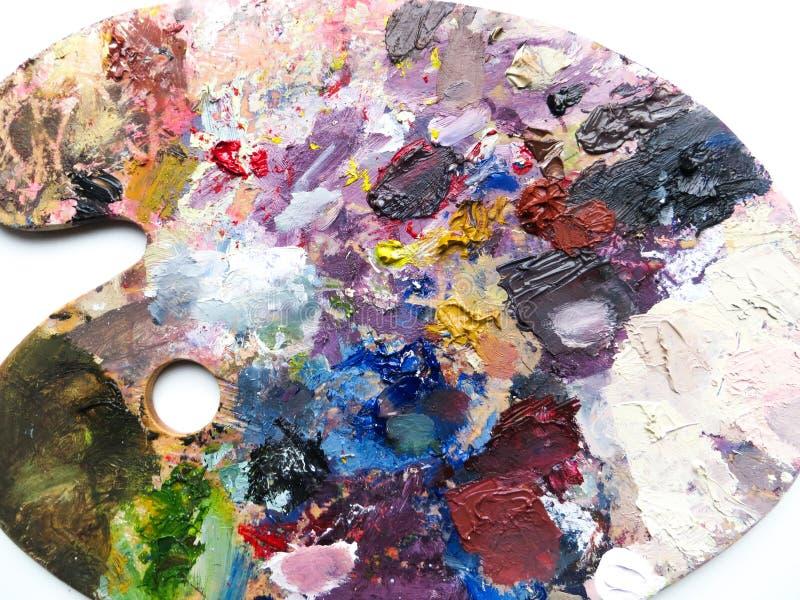 La paleta de los artistas con colores se mezcla sobre el fondo blanco ilustración del vector