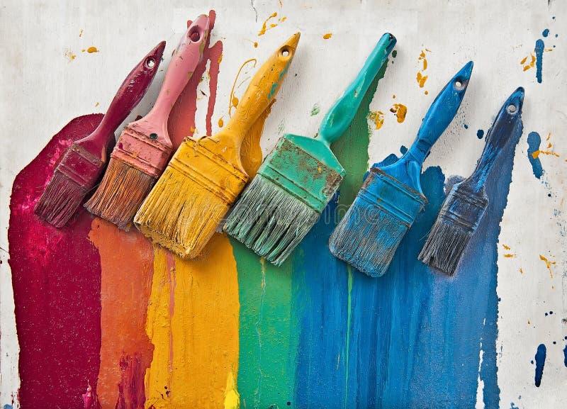 La paleta de los cepillos coloridos del arco iris con la pintura foto de archivo