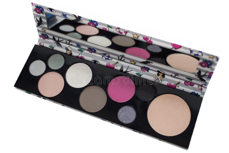 La paleta del cosmético multicolor compone con un espejo, paleta de la sombra de ojos, textura colorida de las sombras, aislada e imágenes de archivo libres de regalías