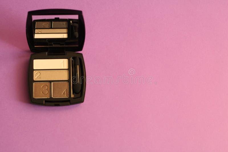 La paleta neutral de sombras de ojos en el caso, pulveriza el fondo rosado, espacio de la copia libre imagen de archivo