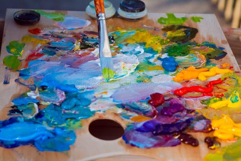 La palette en bois du peintre a couvert de mélange des peintures à l'huile lumineuses fraîches, la brosse avec une peinture verte photographie stock libre de droits