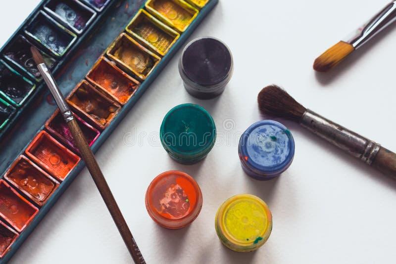 La palette lumineuse et colorée de couleurs se trouve sur le papier blanc d'aquarelle avec plusieurs brosses pour le dessin image libre de droits