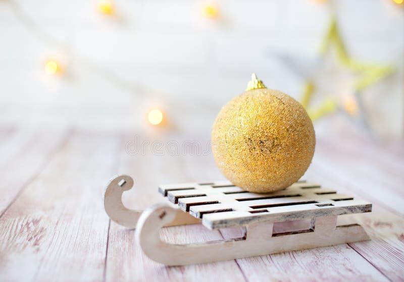 La palla brillante di Natale sulla slitta di legno del giocattolo sul fondo leggero del bokeh con goolden la stella Invito di nuo immagine stock libera da diritti