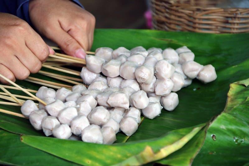 La palla cruda della carne di maiale con il bastone di legno e due mani sulla banana coprono di foglie immagini stock