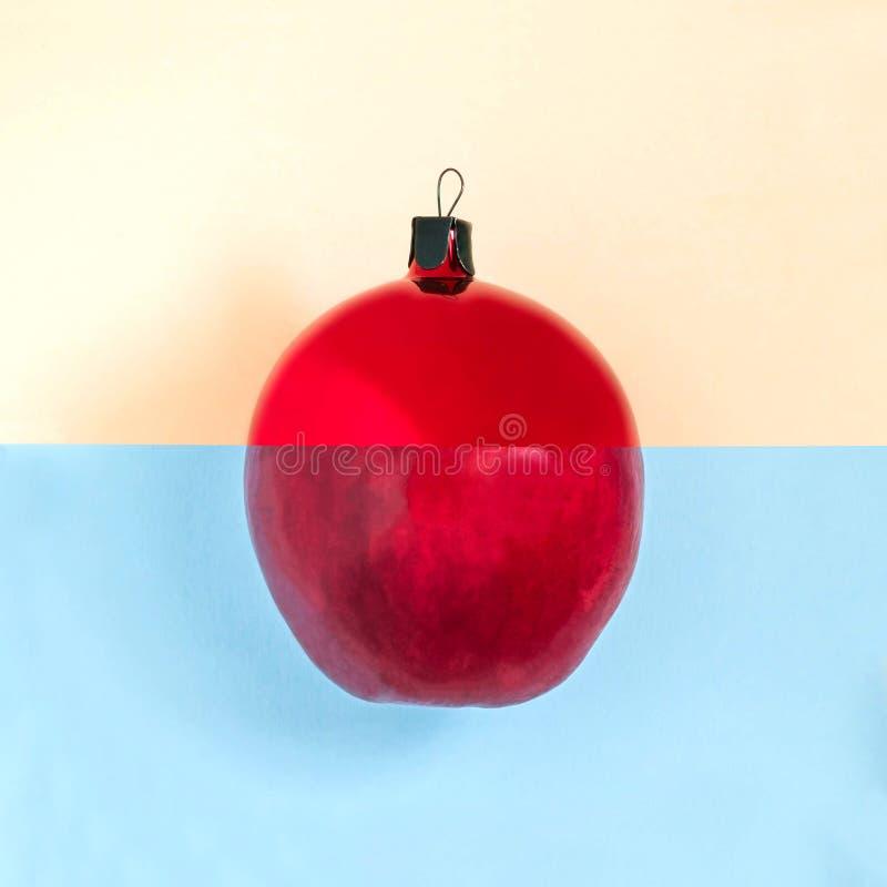 La palla e la mela di Natale sono collegate su un fondo di due colori immagini stock