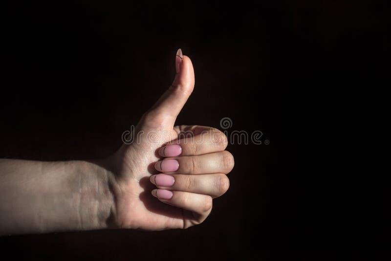 La palma femenina apretada en un puño con un pulgar ampliado para arriba, la muestra es excelente foto de archivo libre de regalías