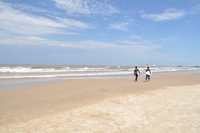 LA PALOMA, URUGUAI - 22 DE JANEIRO: Os surfistas andam na praia do La Paloma, Rocha, Uruguai imagem de stock royalty free