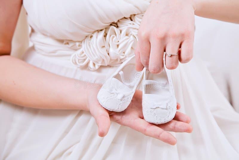La pancia della donna incinta con i bottini bianchi immagini stock