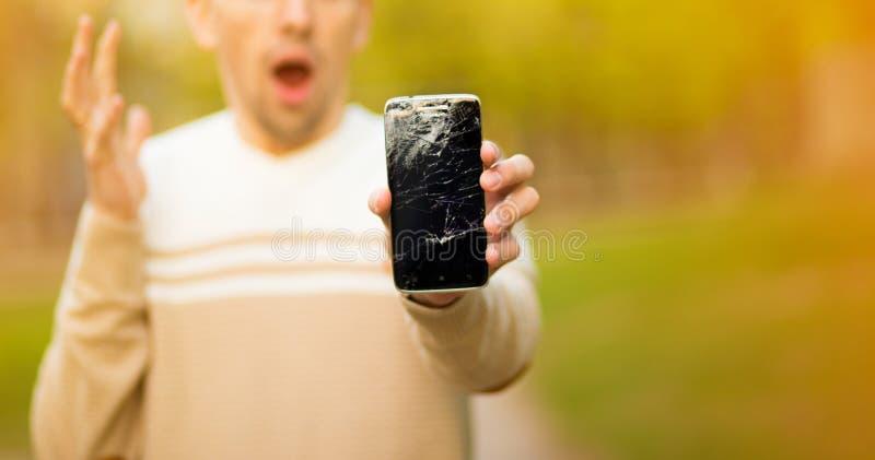 La pantalla quebrada del smartphone del control del hombre joven subrayó con la mano en la cabeza, chocada con la cara de la verg imagenes de archivo