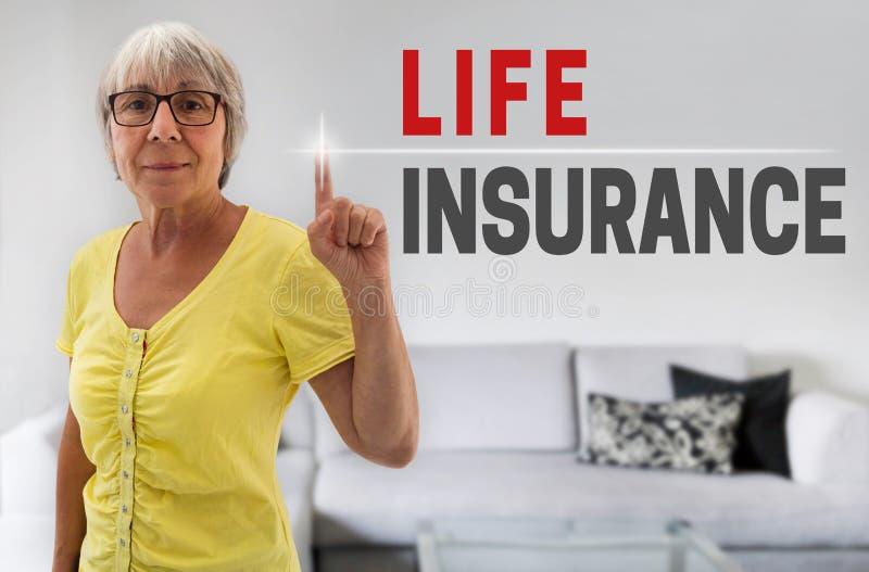 La pantalla táctil del seguro de vida es mostrada por la mujer mayor fotografía de archivo
