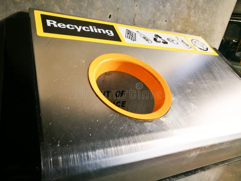 La papelera de reciclaje con la etiqueta amarilla en cierre para arriba fotografía de archivo libre de regalías