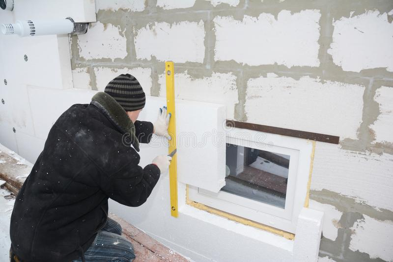 La pared aislador de la casa del contratista de obras con el aislamiento de la espuma de poliestireno cubre en áreas problemática foto de archivo