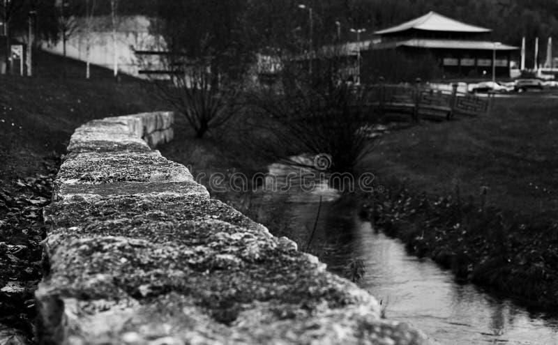 La pared al lado de un pequeño río hacia fuera en el parque urbano de leoben imagen de archivo