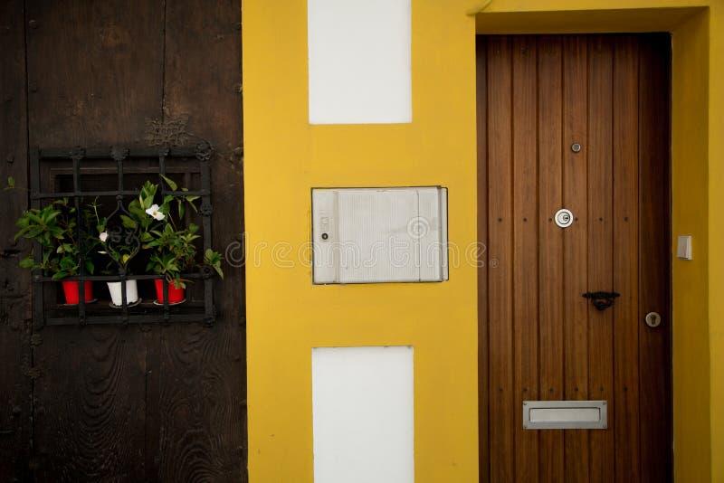 La pared amarilla brillante Puertas de madera imagen de archivo