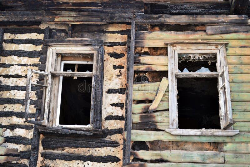 La pared dañada de la casa del fuego y de dos ventanas con el vidrio quebrado en los rayos del sol poniente en la primavera foto de archivo