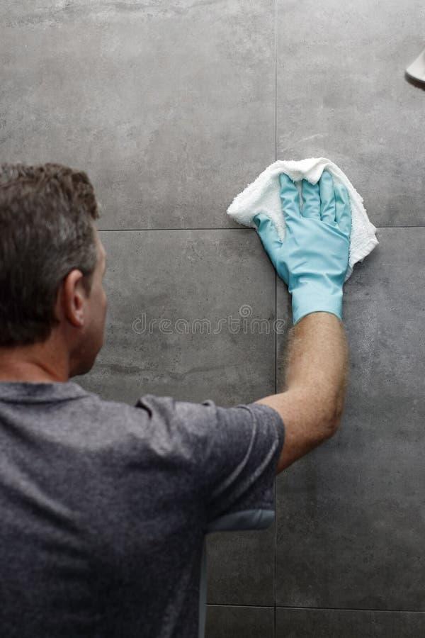 La pared de la ducha del lavado del hombre con un trapo mientras que lleva un verde protege imagen de archivo libre de regalías