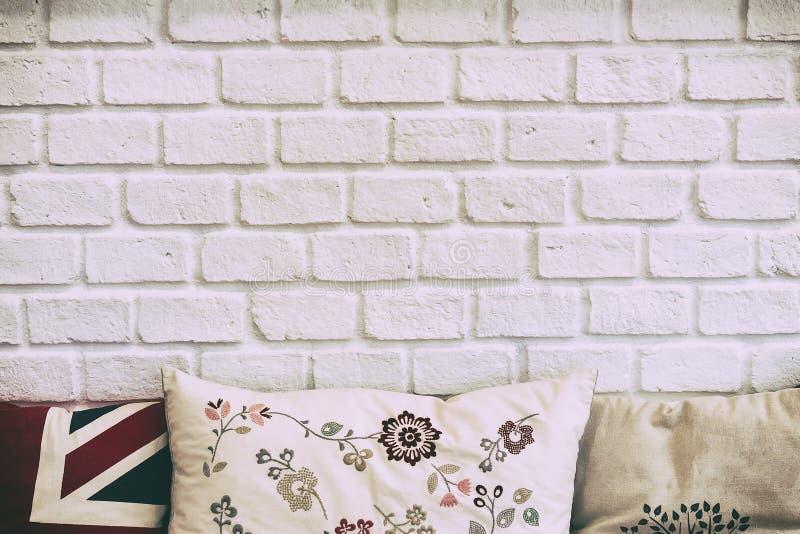 La pared de ladrillo blanca con las almohadas fotos de archivo
