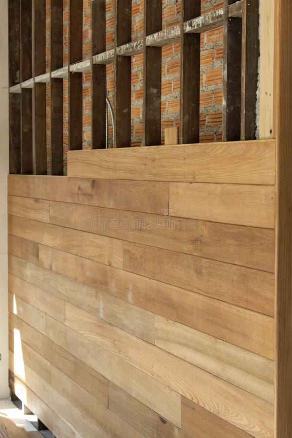 La pared de ladrillo se cubre con los paneles de madera está bajo construcción imagenes de archivo
