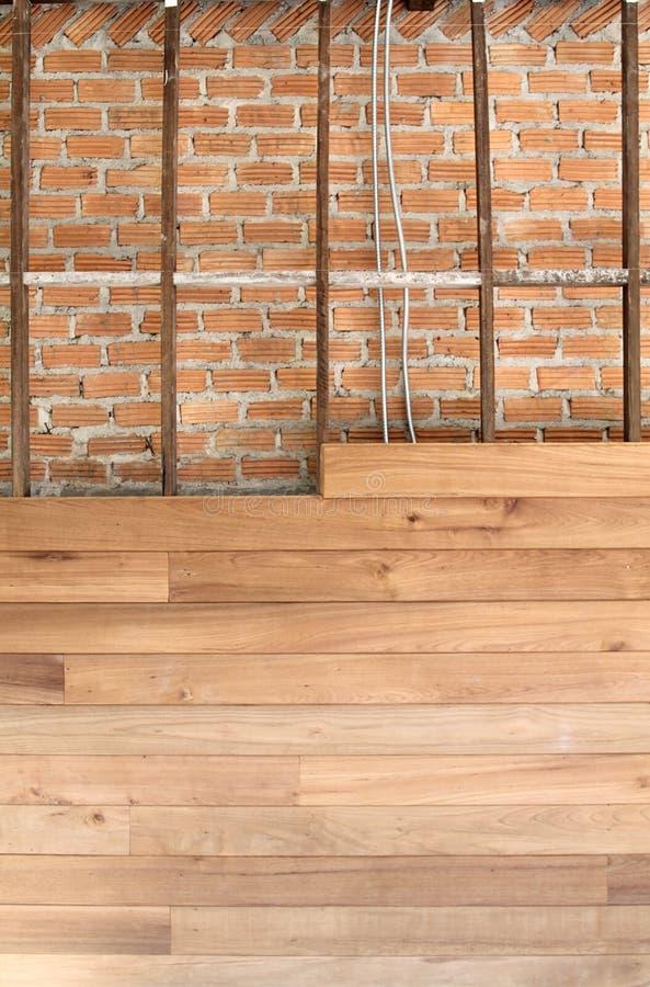 La pared de ladrillo se cubre con los paneles de madera está bajo construcción fotografía de archivo