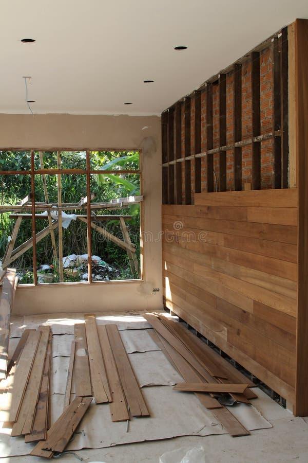 La pared de ladrillo se cubre con los paneles de madera está bajo construcción imagen de archivo