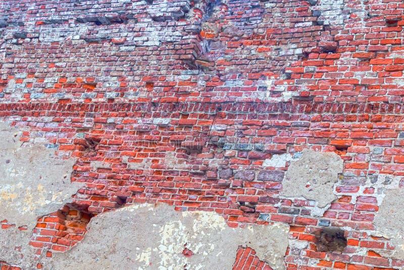 La pared de ladrillo vieja de la torre de la pared arruinó de piedras de macadán cubierta mucho con el diseño del fondo del yeso  fotos de archivo
