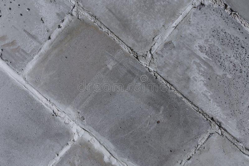 La pared de las paredes viejas de la ciudad del fragmento diagonal de los bloques concretos, grises, porosos imágenes de archivo libres de regalías