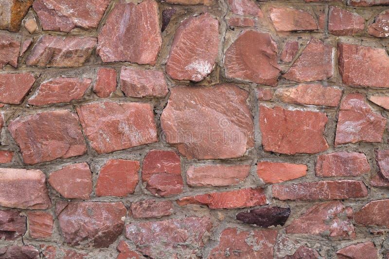 La pared de las piedras crudas grandes del color rojo, granito del granito del fondo no uniforme imagen de archivo