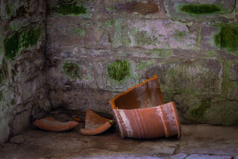 La pared de piedra vieja del und gris y el pote de arcilla quebrado foto de archivo libre de regalías