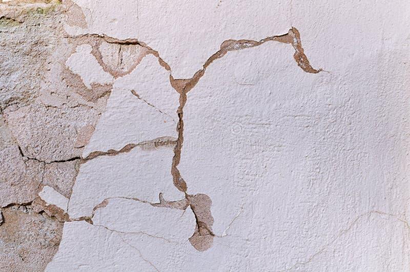 La pared de piedra vieja texturizada con las grietas curvadas y la peladura envejecieron el estuco en tonos naturales imagen de archivo libre de regalías