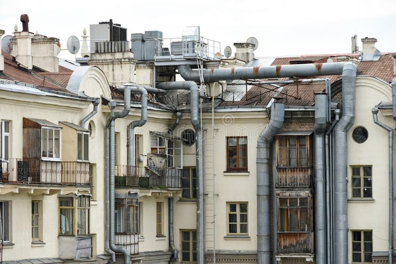 La pared de un edificio residencial viejo en la ciudad con los tubos grandes del sistema de cableado y de condicionamiento del ca fotos de archivo libres de regalías
