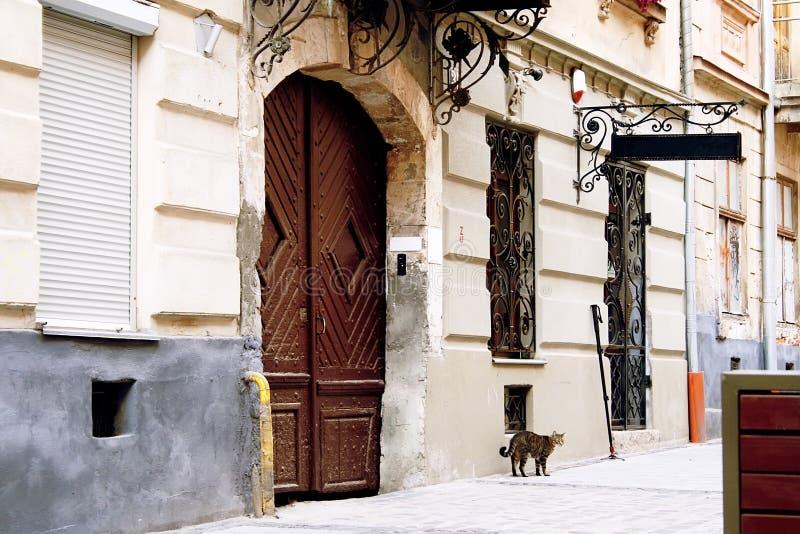 La pared de una casa vieja con una puerta de madera grande, un letrero y las barras del labrado-hierro en las ventanas fotografía de archivo