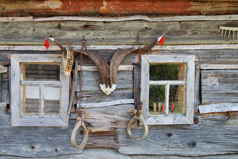 La pared de una casa vieja del pueblo, adornada con los cuernos fotografía de archivo libre de regalías