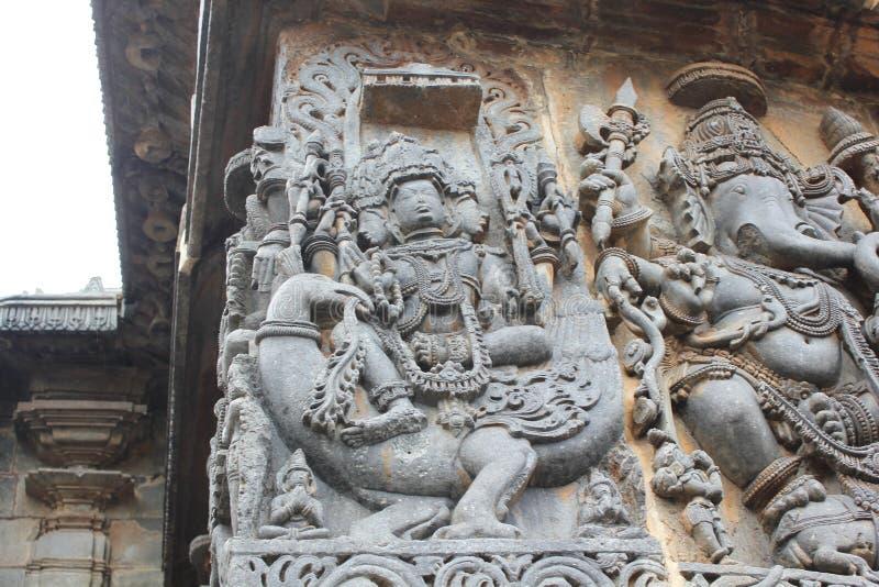 La pared del templo de Hoysaleswara talló con las esculturas de dios de Lord Brahma de la creación y de dios de Lord Ganesha Elep fotografía de archivo libre de regalías