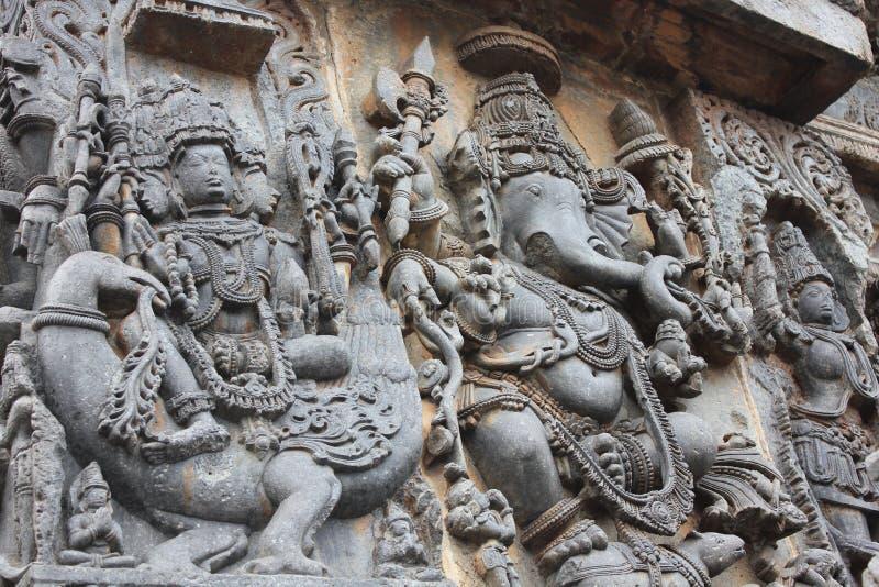 La pared del templo de Hoysaleswara talló con las esculturas de dios de Lord Brahma de la creación y de dios de Lord Ganesha Elep foto de archivo