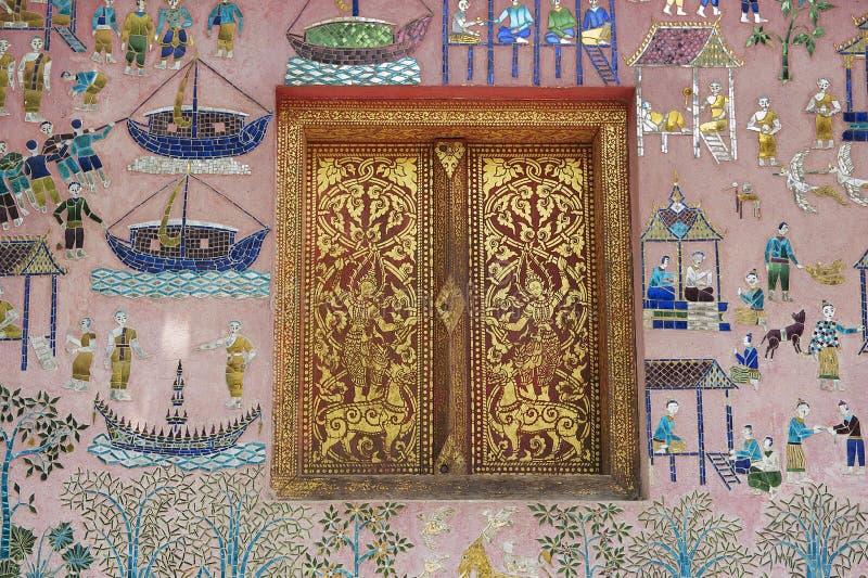 La pared exterior con el mosaico y el oro hermosos pintó la ventana del pabellón en el templo de la correa de Xieng en Luang Prab foto de archivo