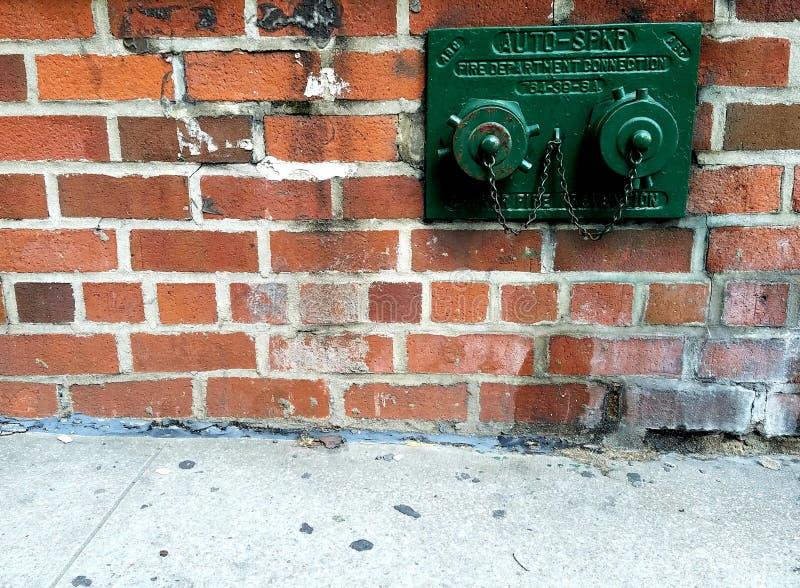 La pared exterior de la ciudad realista y el sistema de rociadores al aire libre del agua pintaron verde imagenes de archivo