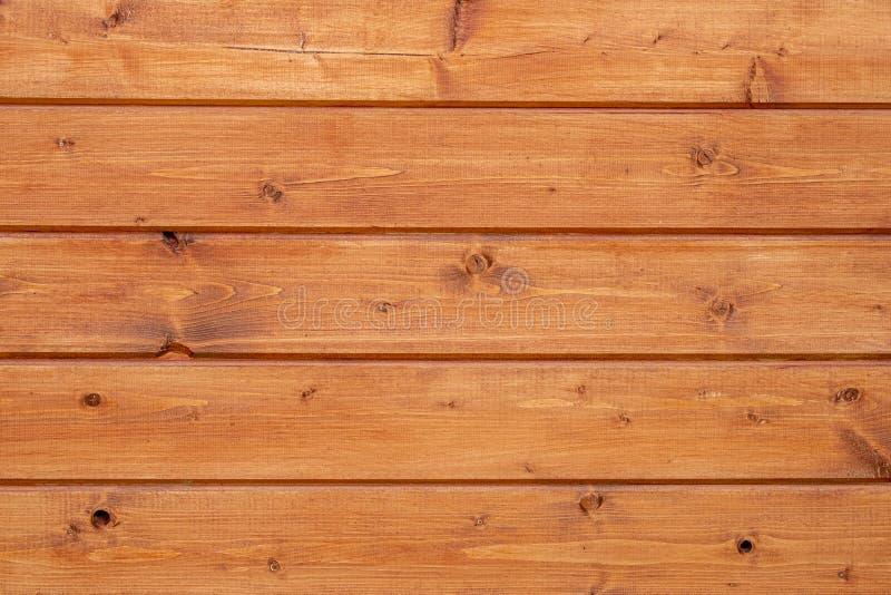 La pared se cubre con los tableros de madera y se cubre con la impregnación protectora anaranjada imagen de archivo libre de regalías