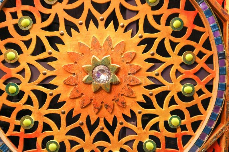 La pared tallada de madera, coloreada, brillante, abigarrada con las flores, estrellas, modelos, coloreó las piedras de diversos  fotos de archivo libres de regalías